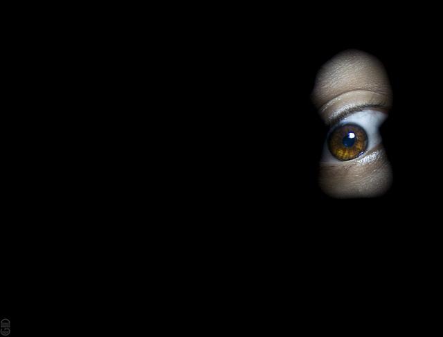 Hombre con fobias mirando por una cerradura; claustrofobia
